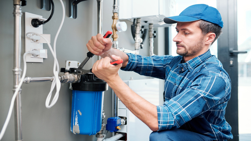 Young plumber or technician in workwear using pliers while installing or repairing system of water filtration